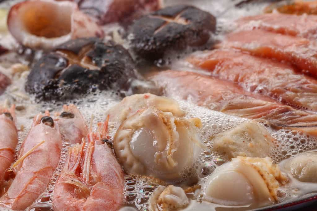 煮立った石狩鍋の中のエビ・ホタテ・秋鮭・椎茸