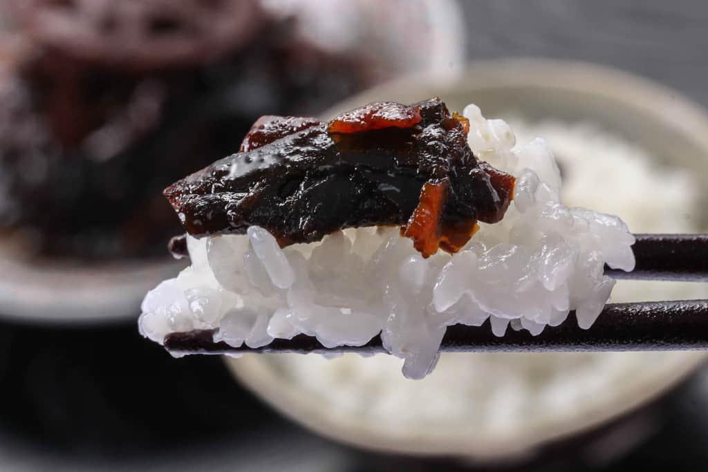 野菜昆布をご飯と一緒に食べる、ご飯にのせた野菜昆布を箸でつまむ