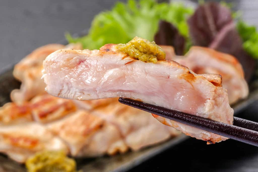 みやざき地頭鶏むね肉のレア焼きソテーに柚子胡椒をのせて箸で持ち上げる