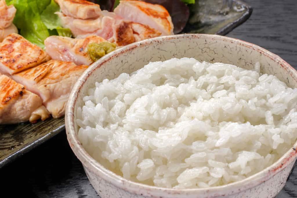 茶碗に盛った白いご飯とみやざき地頭鶏ムネ肉のレア焼きソテー