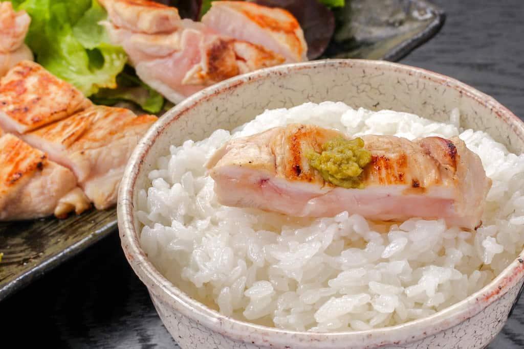 白いご飯の上に一切れのみやざき地頭鶏のむね肉炒めを乗せる