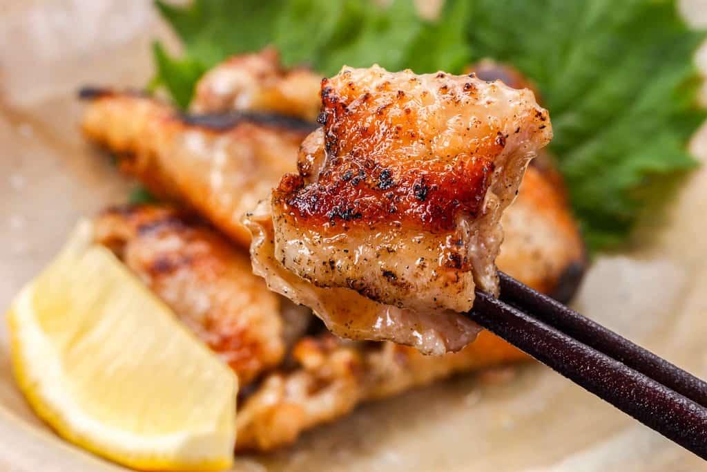 みやざき地頭鶏の鶏皮焼きを箸で持ち上げる