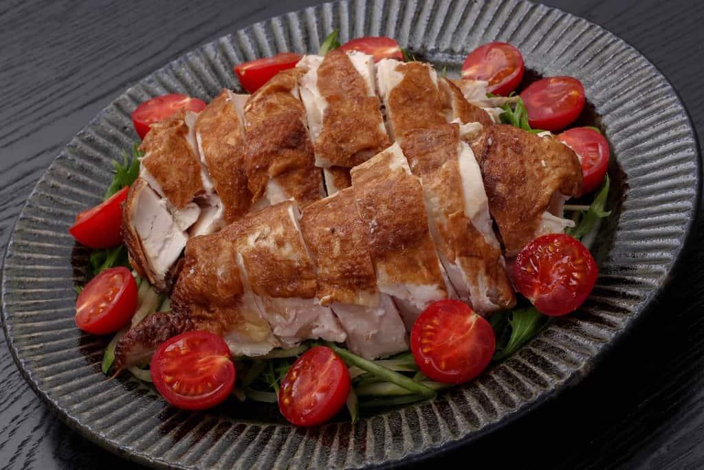 トマトや水菜と一緒に盛り付けた劉家荘の焼鶏のムネ肉部分