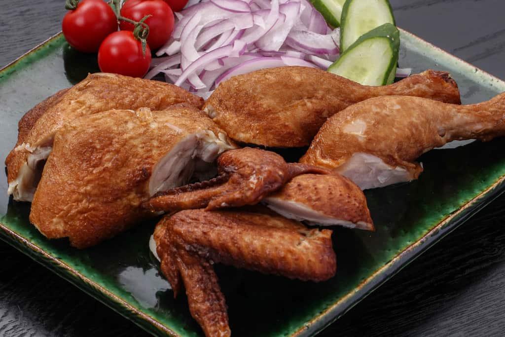 トマトや玉ねぎと皿に盛り付けた劉家荘の焼鶏(手羽元、手羽先、モモ肉)