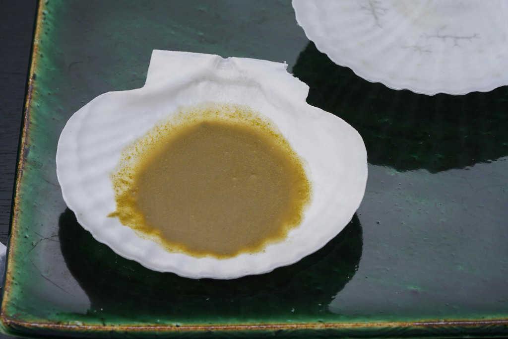 帆立貝殻の中の肝ソースと帆立出汁をかき混ぜる