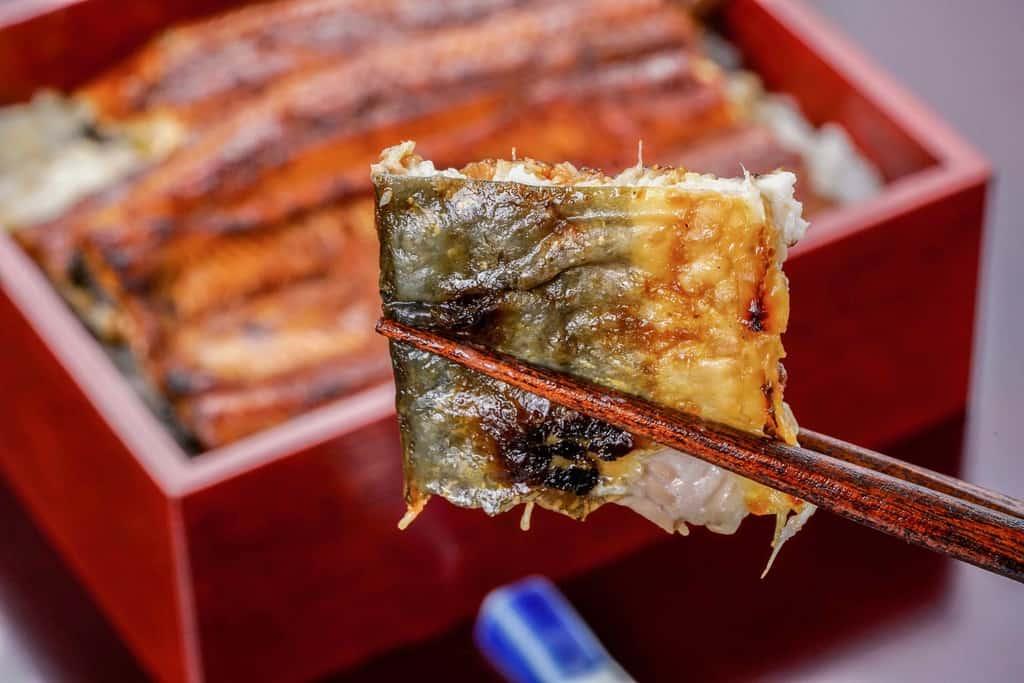 皮の焼き加減がわかるように箸で持った大五うなぎ工房のうなぎ蒲焼「駿河大五郎」一切れ、うなぎ蒲焼の皮、うなぎ蒲焼の焼き目