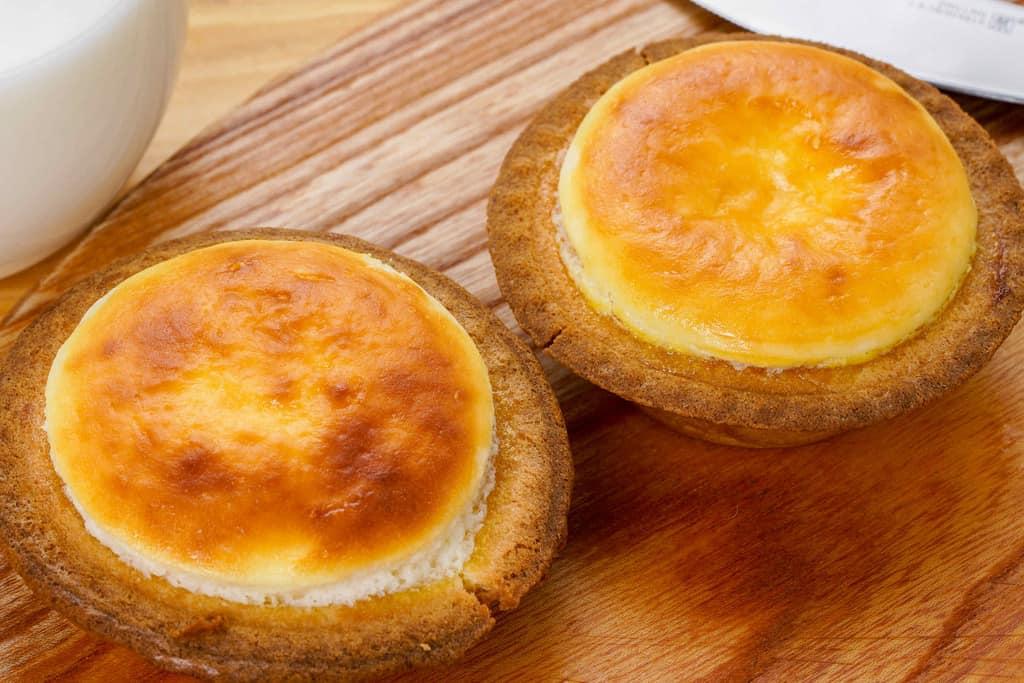 オーブンで焼き上げた洋菓子きのとやの「焼きたてチーズタルト」2個、カッティングボードの上の焼きたてチーズタルト