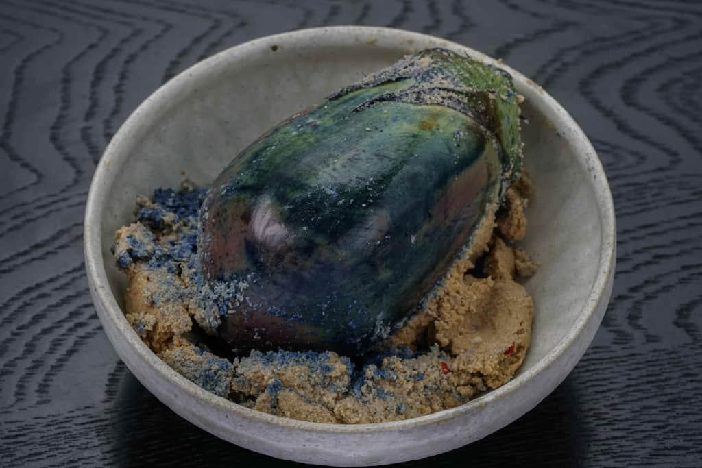 北野農園の泉州水なすぬか漬け(浅漬け)1個のぬかを皿の上で落とす