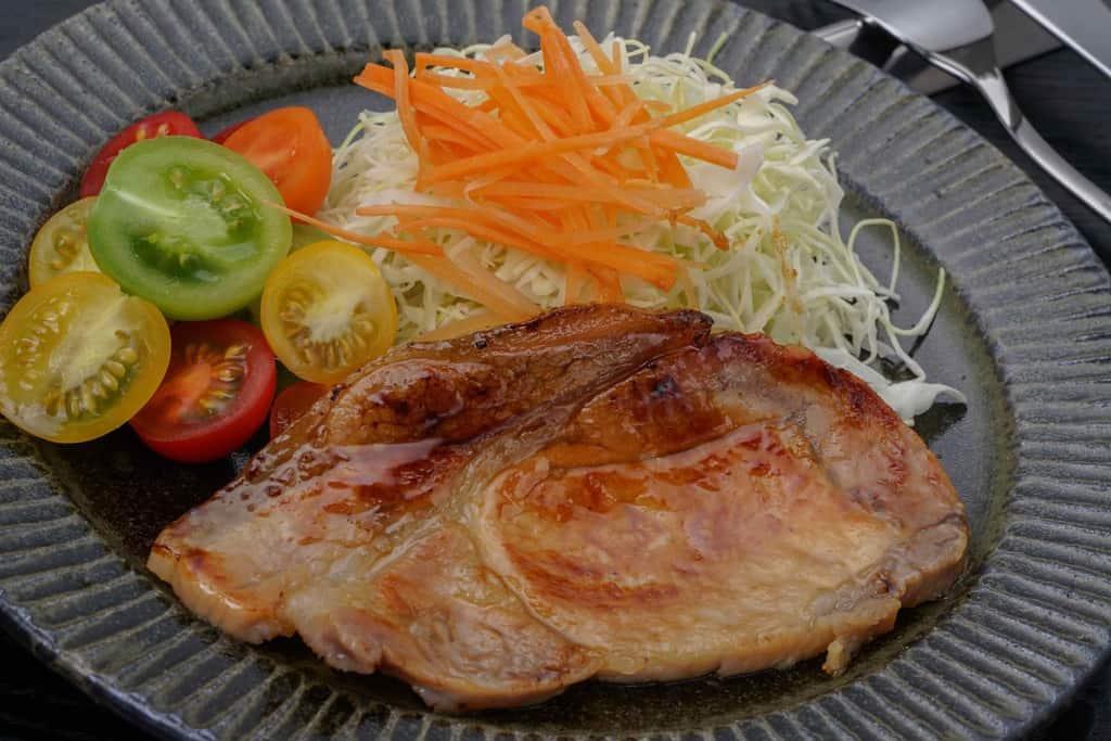ミニトマト・キャベツの千切りと共に皿に盛り付けた豚肉味噌漬け厚切り1枚