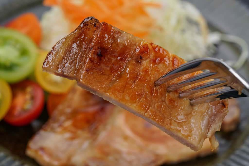 フォークに刺した1切れの豚肉味噌漬け