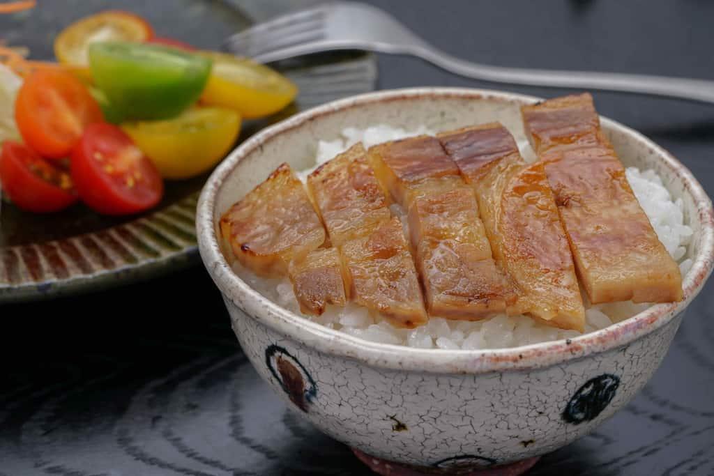 焼いた豚肉味噌漬け5切れをご飯の上に乗せる