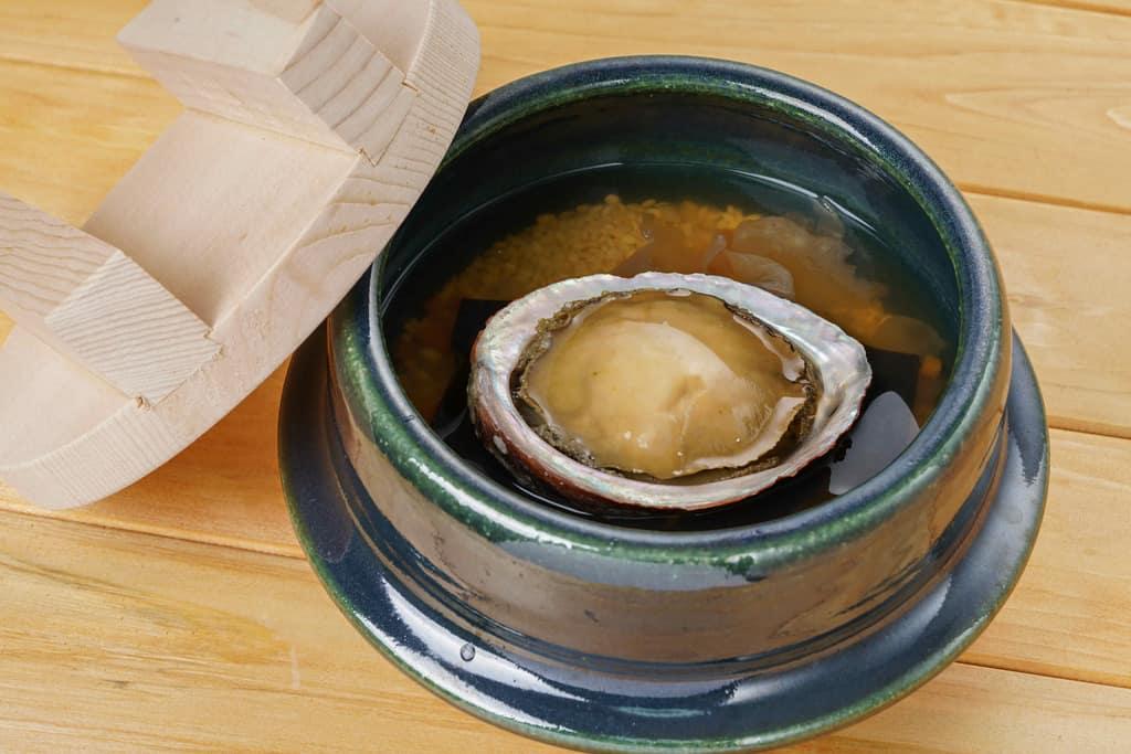 土鍋の中の米と調味液に野菜を加えてアワビの姿煮を乗せる、鮑の炊き込みご飯