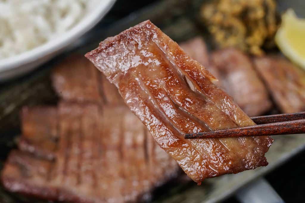 食べやすい大きさにカットしたたんや善治郎の牛たん塩焼きを箸でつまむ