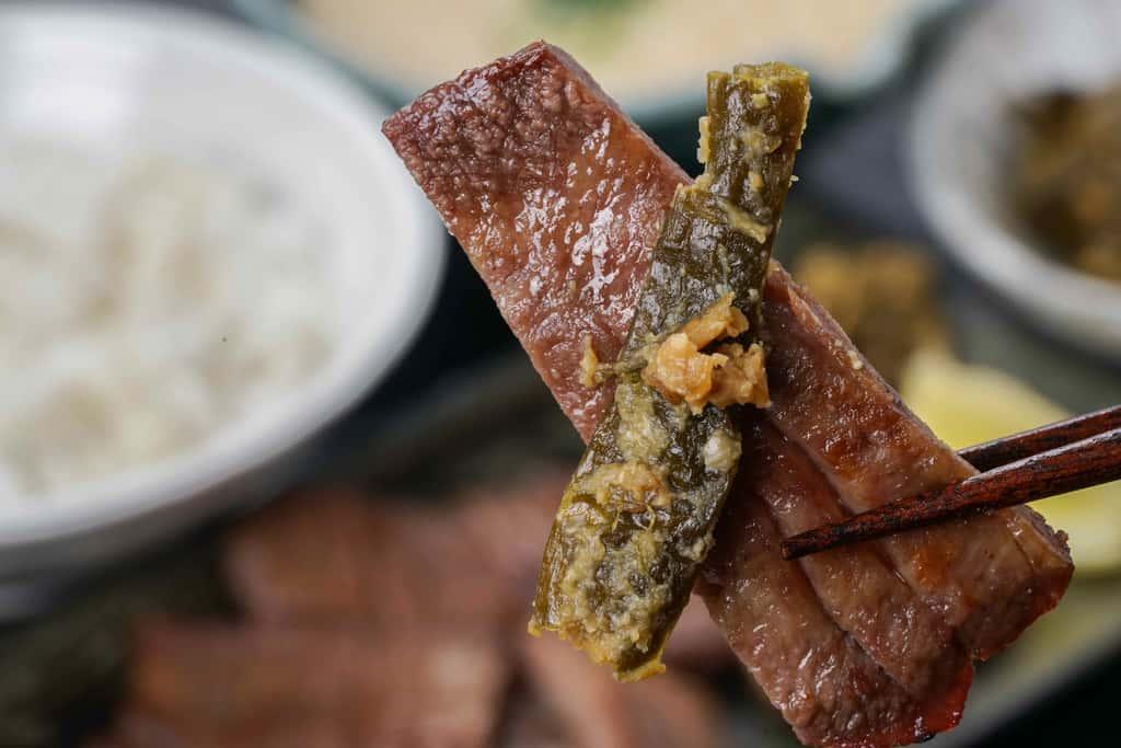 たんや善治郎の牛たん塩と一緒に南蛮味噌漬けを箸でつまむ
