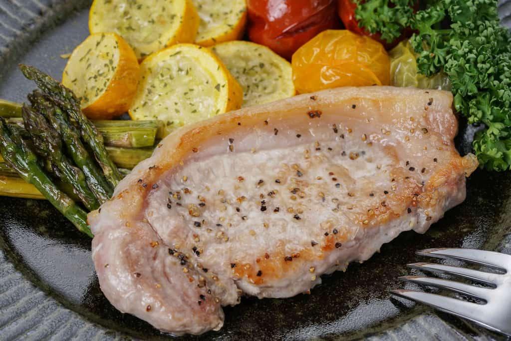 グリル野菜と一緒に皿に盛り付けた塩胡椒で焼いた天草梅肉ポークのロース肉100g、天草梅肉ポークのロース肉100g・アスパラ・ズッキーニ・ミニトマト