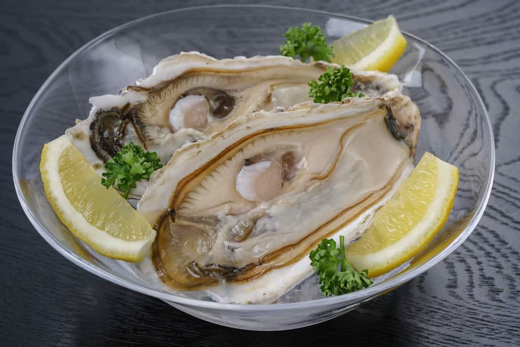 北釧水産から届いた北海道厚岸産の生牡蠣2個とカットレモン、氷をしいたガラスの器に入った生牡蠣2個