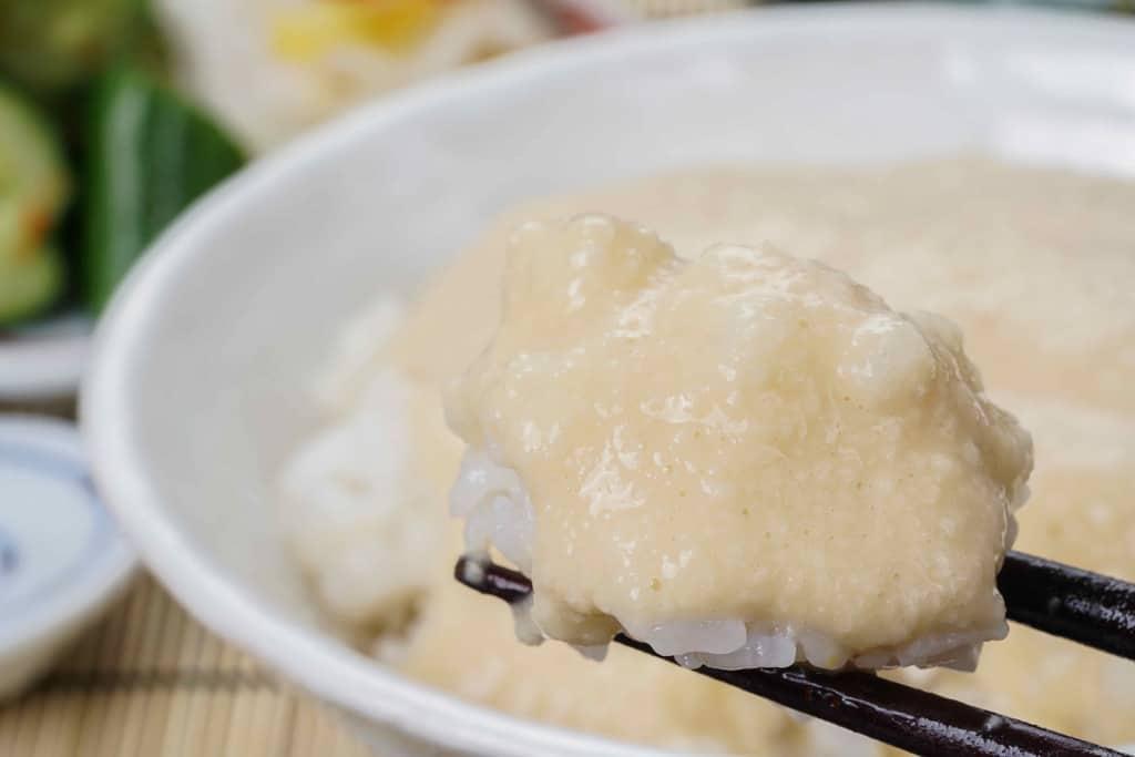 ご飯にかかった浅草むぎとろの味付とろろ、とろろご飯を箸でつまむ