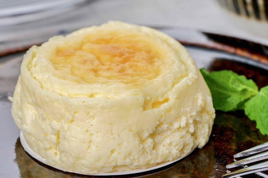 皿の上のスナッフルスのチーズオムレット1個・ミントの歯・フォーク、スフレタイプのチーズケーキ