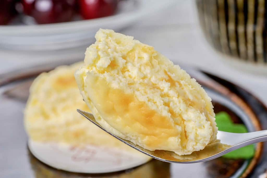 フォークで半分にカットしたペイストリースナッフルスのチーズオムレットを持ち上げる、チーズオムレットの断面