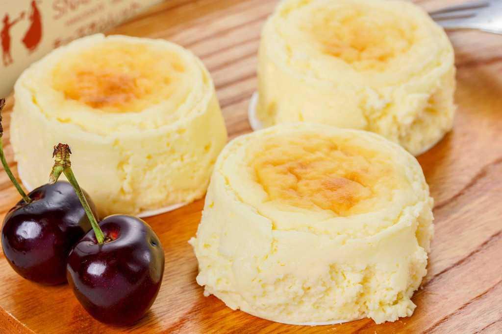 カッティングボードの上のチーズオムレット3個とアメリカンチェリー、スナッフルスのチーズケーキ