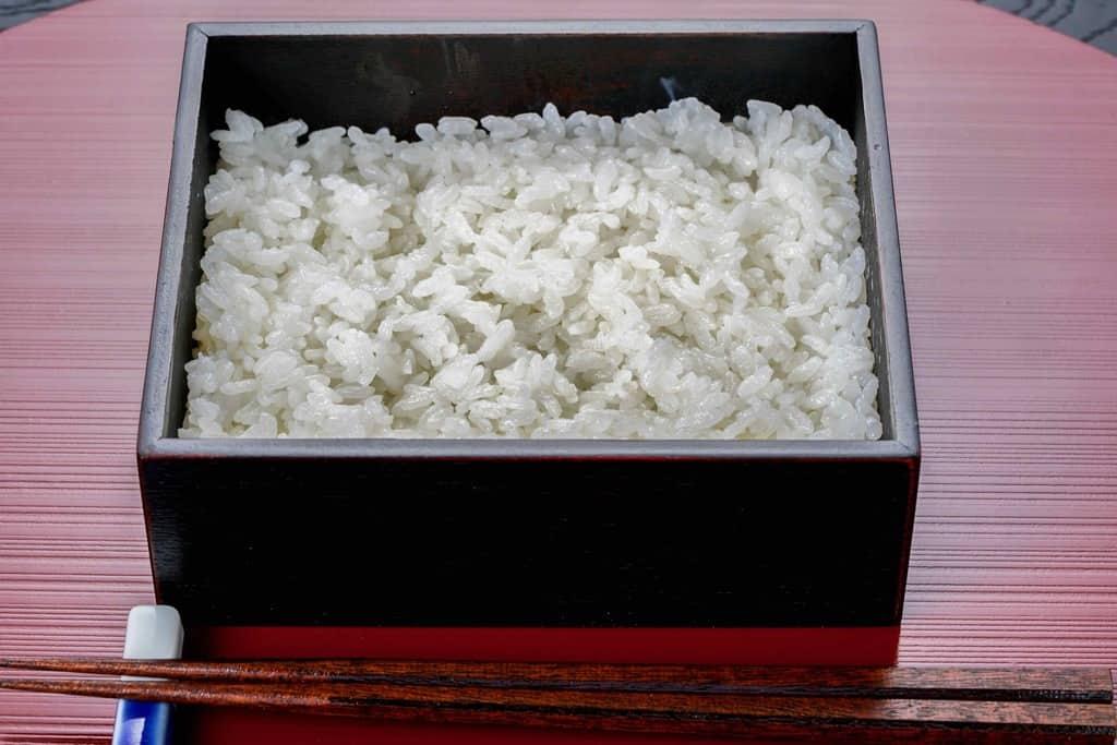 ご飯の入ったうな重用の重箱と箸、重箱に炊きたてのご飯を詰める