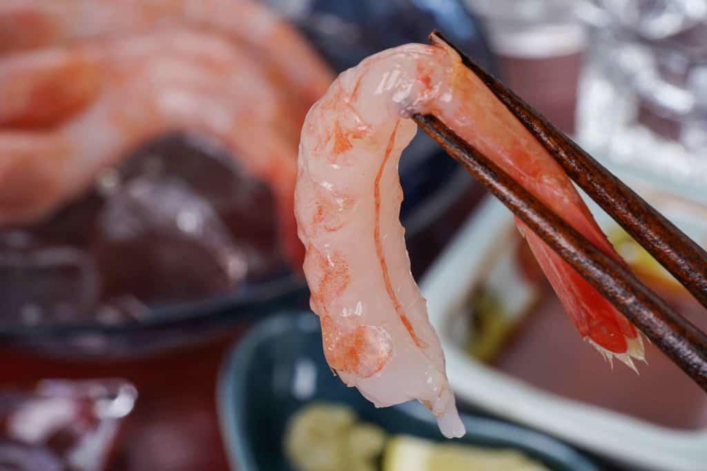 箸でつまんだ遠藤水産の特大甘えび、殻をむいた甘えびを刺身で