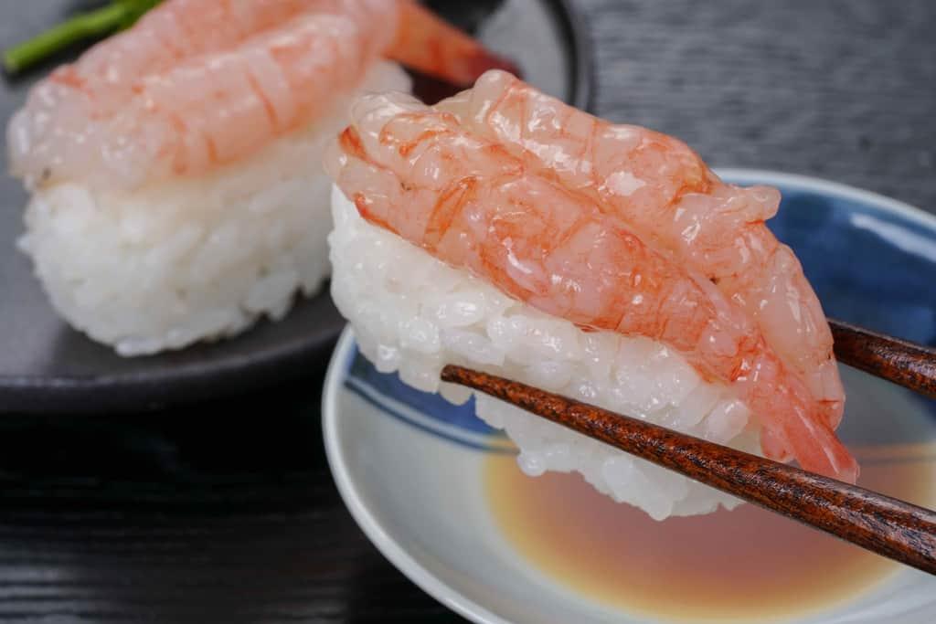 箸でつまんだ甘えびの寿司