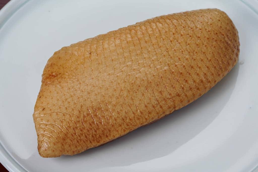 袋から取り出して皿に盛り付けた嵐山たなかの合鴨スモーク(ロース肉)、合鴨スモークの皮側