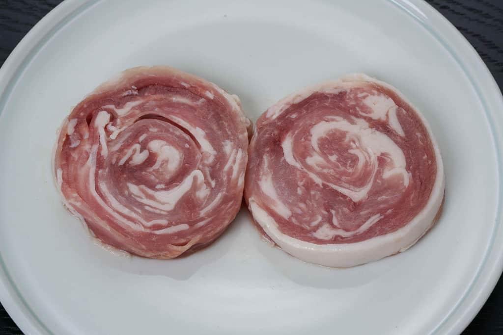皿に乗ったうまかもんさつまの国産黒豚ロールステーキ2つ