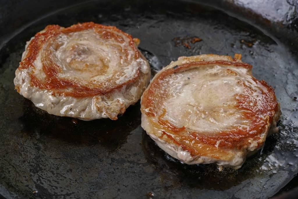 鉄フライパンの上でこんがりと焼きあがった2枚の黒豚ロールステーキ