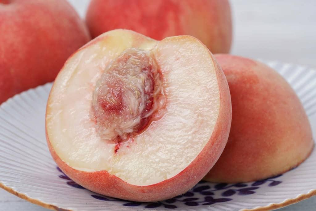 1玉を半分に割って断面が見える状態で皿に乗せたJAふくしま未来の桃「伊達の蜜姫」、半分に割ったモモ