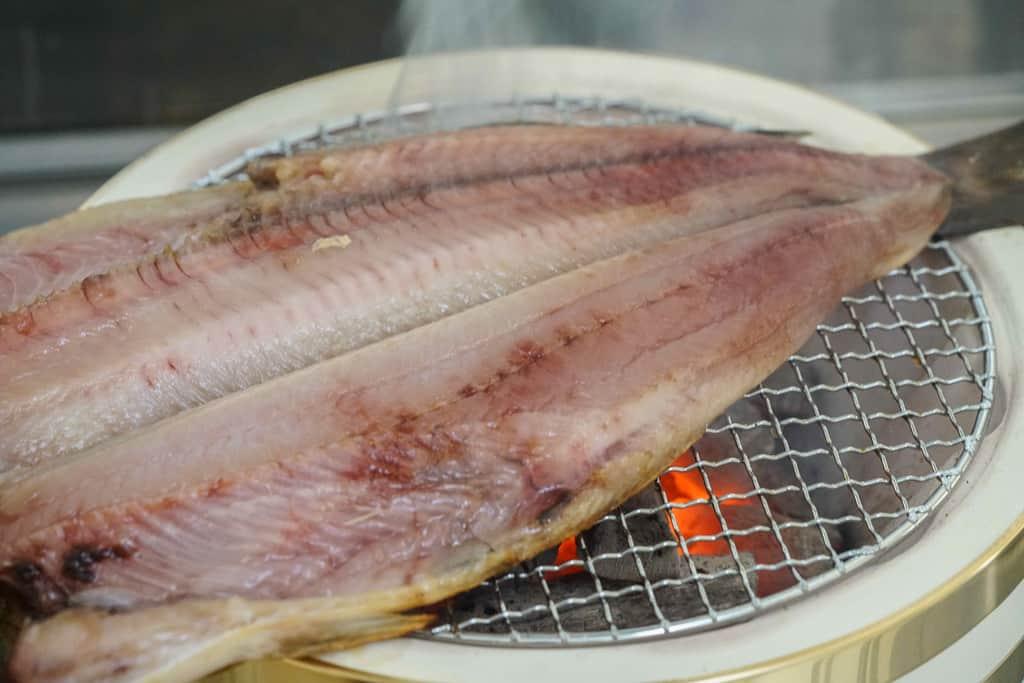 七輪の上で焼かれる高野鮮魚店の特大根ボッケの開き、根ホッケの炭火焼き