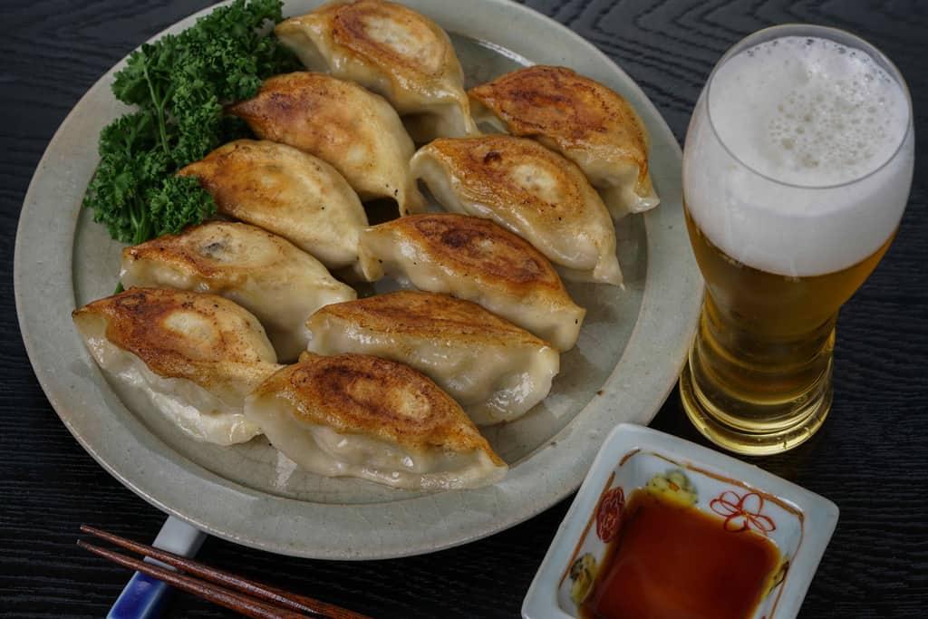 焼き目を上にして皿に盛り付けた蓮月の手づくり焼き餃子10個・ビール・タレ・箸