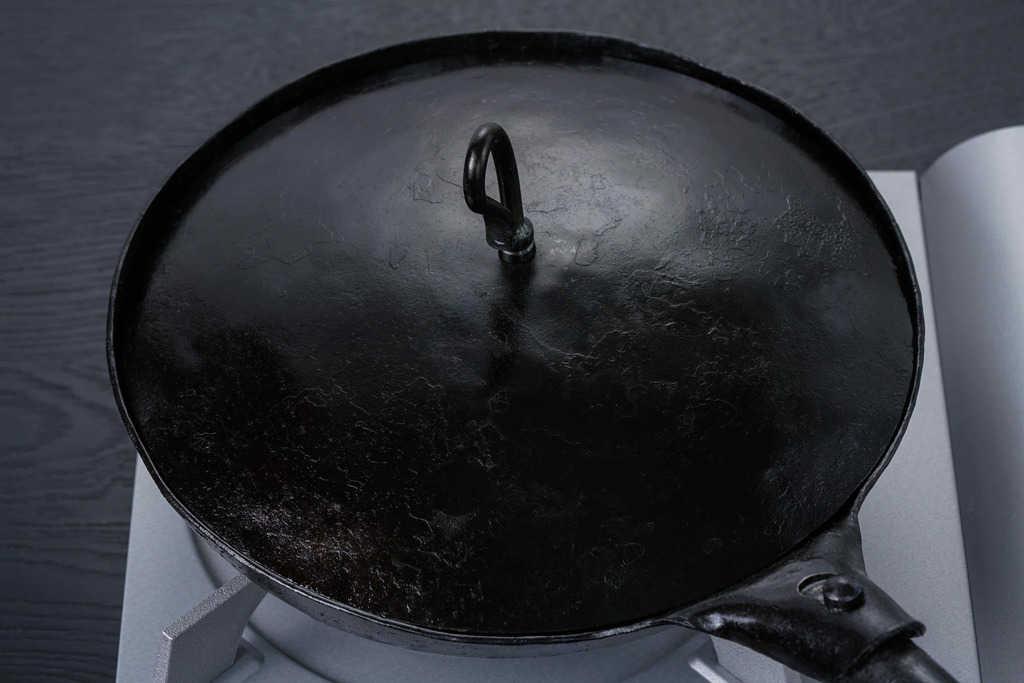 コンロの上にある蓋をした鉄のフライパン