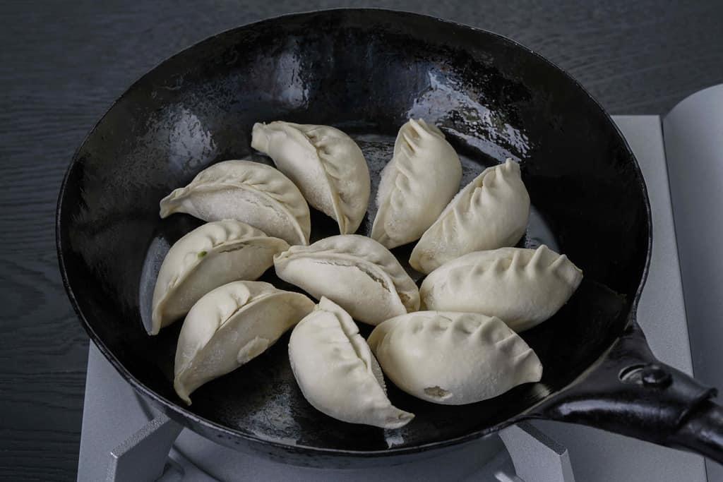 フライパンに並べた冷凍状態の蓮月の手づくり焼き餃子10個