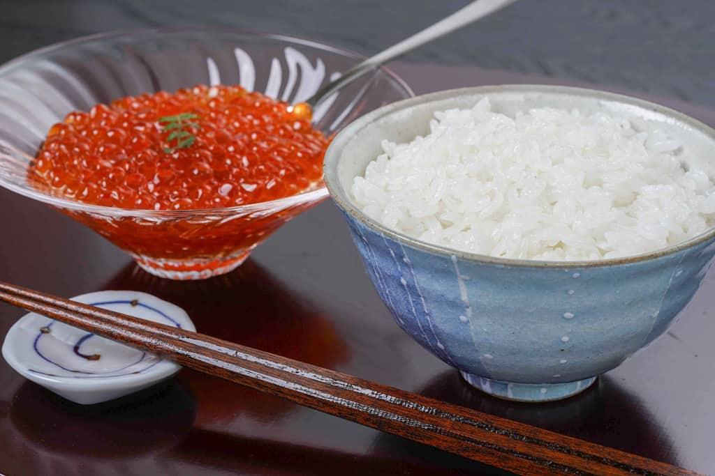 茶碗一杯の白飯・ガラスの器に入ったいくら醤油漬け・箸置き・箸