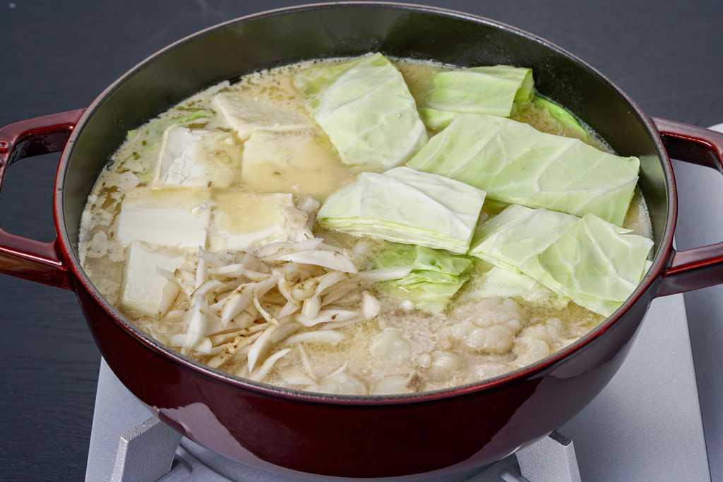 蟻月の白のもつ鍋に野菜を入れる、スープ・モツ・キャベツ・豆腐・ごぼうが入ったstaub鍋