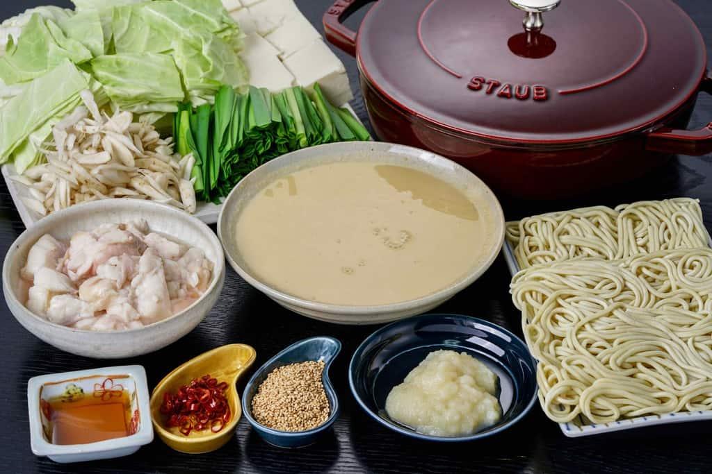 もつ鍋用の具材(牛もつ・スープ・ちゃんぽん麺・おろしにんにく・食用ごま油・ごま・唐辛子・キャベツ・ニラ・豆腐・ごぼう)とstaub鍋