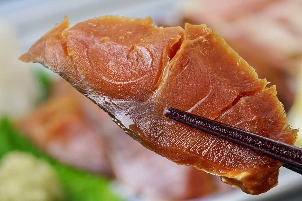 刺身用にカットした竹扇の鯖のへしこ一切れを箸で持ち上げる