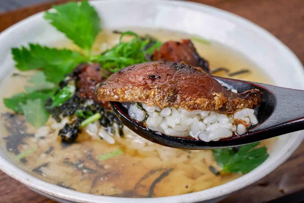 鯖のへしこのお茶漬けをレンゲに入れて 持つ、竹扇の鯖のへしこ茶漬け