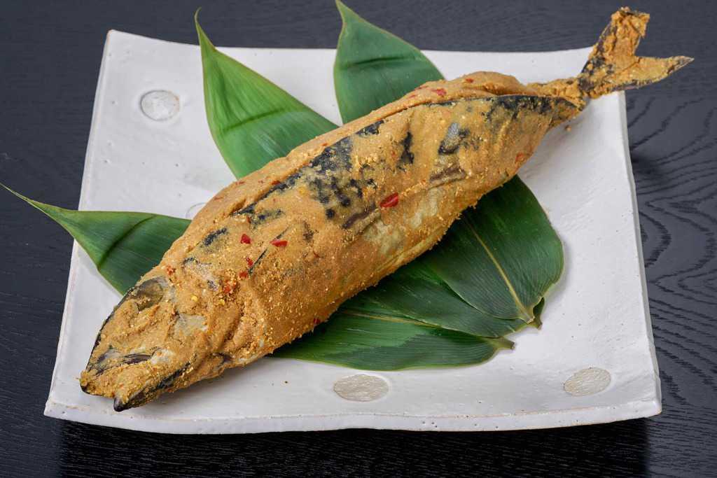 袋から取り出して皿に盛り付けた竹扇(福井県)の鯖のへしこ姿漬け1尾、表面をぬかで覆われた鯖のへしこ
