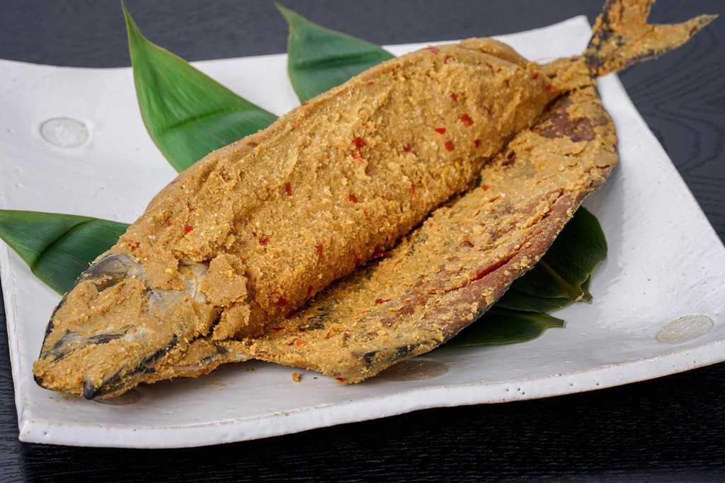 半身を開いて中に詰まった糠が見える状態にした竹扇の鯖のへしこ姿漬け1尾、皿の上の福井名物サバのへしこ