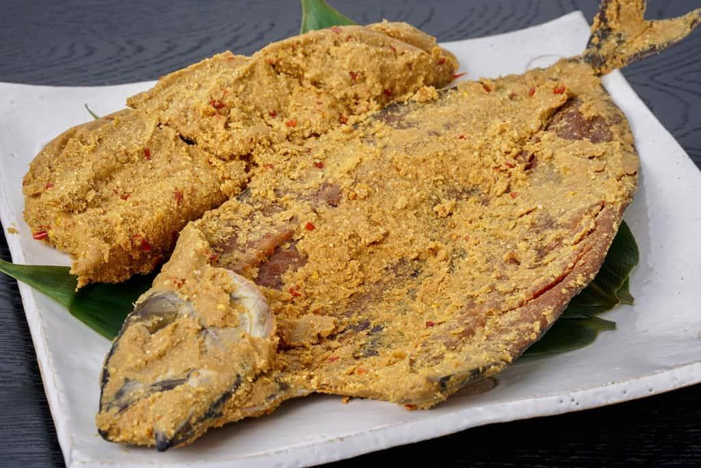 中に詰まった糠床を取り分けて開いた状態で皿に盛り付けた竹扇の鯖のへしこ姿漬け1尾
