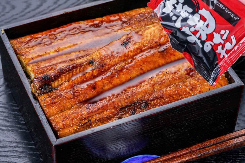 重箱に盛り付けたうなぎ屋かわすい(川口水産)の超特大サイズ国産うなぎ蒲焼にたれをかける、うな重