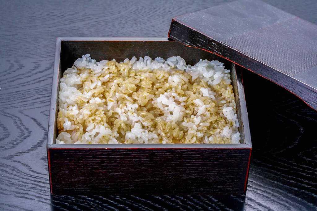 うな重用の角箱に盛り付けた炊きたてご飯にうなぎ蒲焼のたれをかける、うなぎのたれご飯、