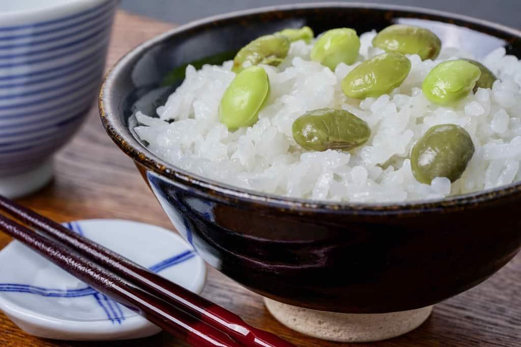 飯椀に盛り付けた枝豆ごはんと湯のみ茶碗と箸、京都の丹波黒大豆枝豆(紫ずきん)で作った枝豆ごはん