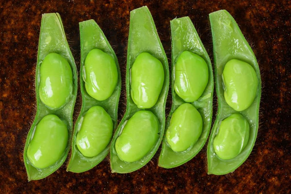 さやの中の豆が見える状態で皿に並べた茹でた毛豆枝豆