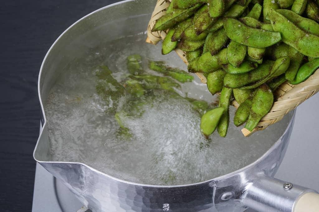 雪平鍋の中で沸騰したお湯に枝豆を入れる、浦田農園の毛豆枝豆をお湯で茹でる