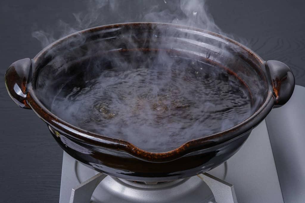 土鍋に入ったきりたんぽ鍋スープから湯気が出る
