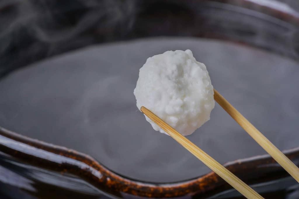 煮立ったスープにだまこもちを入れる、スープが煮立った土鍋・箸でつまんだだまこもち
